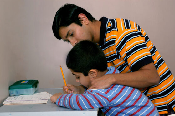 Indian boy with learning challenges being helped by his father