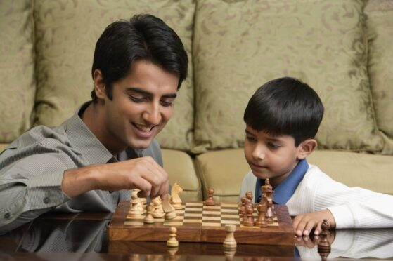 Gifted boy playing chess with his father